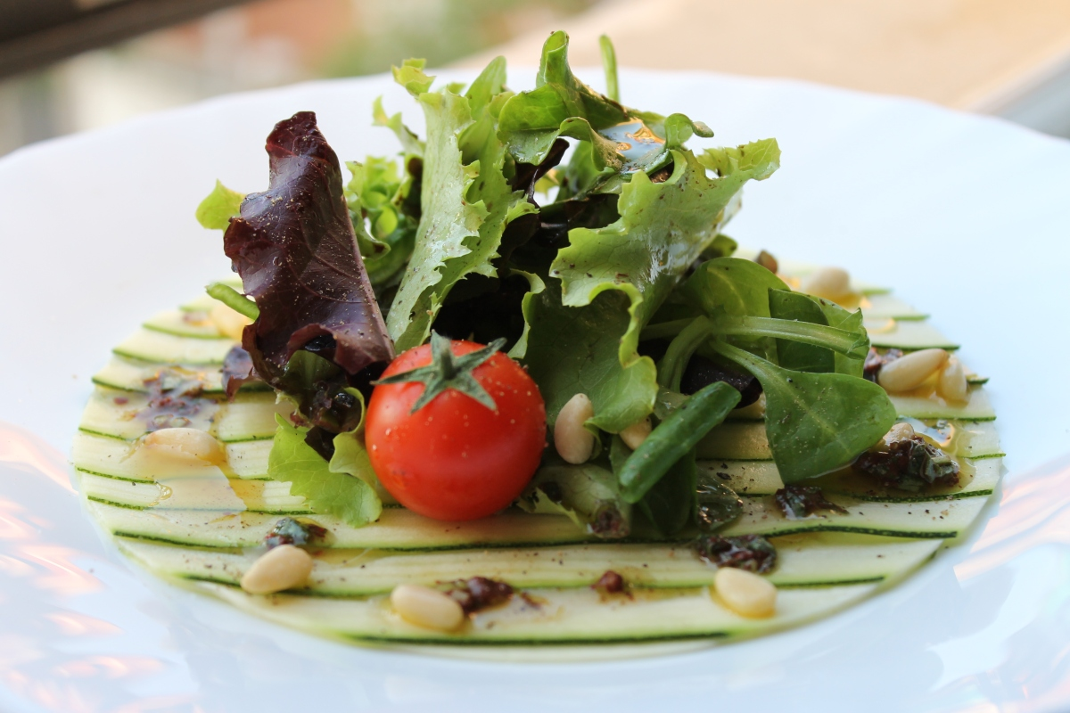 Zucchini carpaccio with black olive dressing and toasted pine nuts